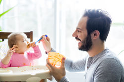 stock-photo-a-father-feeding-his-little-baby-daughter-601414055