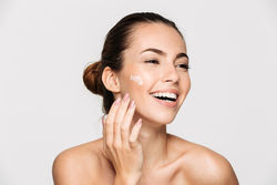 stock-photo-close-up-beauty-portrait-of-a-laughing-beautiful-half-naked-woman-applying-face-cream-and-looking-763618693.jpg
